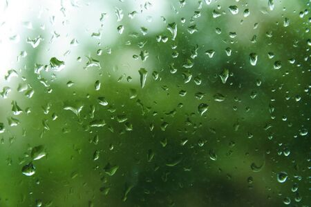 Photo for Beautiful view from window at dim outlines nature backdrop. Water drops on glass with blurred edges. View from window on rainy day. Rain drop on windowpane with blur tree background. - Royalty Free Image