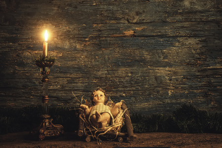 Foto de Christmas card, Child Jesus in his crib and candle on  dark wooden background with copy space. - Imagen libre de derechos