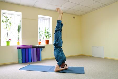 Foto de Young brunette of American origin sits on yoga mat and performs longitudinal twine. - Imagen libre de derechos