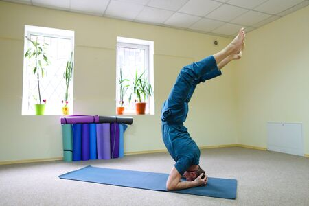 Foto de Young brunette of American origin sits on yoga mat and performs longitudinal twine. Short-haired sportswoman dressed in blue sports pants and blue t-shirt. Room light and spacious, under wall multi-colored yoga mats. Concept of to maintain body in good physical shape, in care of health. - Imagen libre de derechos