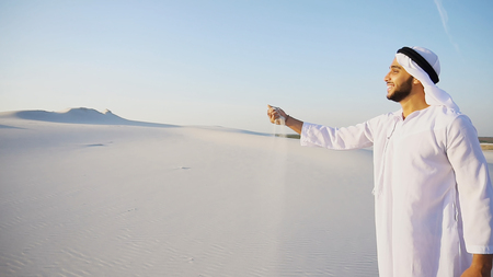 Photo for Muslim smiles, leans over and takes sand in hands, blowing in wind. - Royalty Free Image