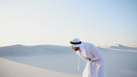 Photo for Worn-out Emirati man bends from pain and clings to stomach, suffers from severe pain and suffers with all strength, standing in midst of bottomless desert with snow-white sand on sunny summer day. Swarthy Muslim with short dark hair dressed in kandura, long, spacious dress made of white, unpainted cotton with knitted lace cap, gafia, over which headscarf tied. Concept of Arab and Muslim men, United Arab Emirates and beautiful landscapes, advertisement of pharmaceuticals and medicines, deteriorated state of health and prevention of treatment of diseases, national clothing of Emirates. - Royalty Free Image