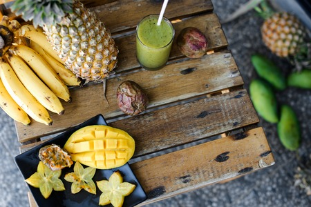 Photo for Carambola with mango in plate near bananas and pine-apple on wooden table. Concept of exotic fruits and tropical healthy food. - Royalty Free Image