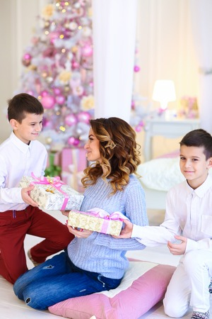 Photo pour Two caucasian sons gifted present for mother near decorated fir tree. Concept of christmas tipme and winter holidays, happy family. - image libre de droit