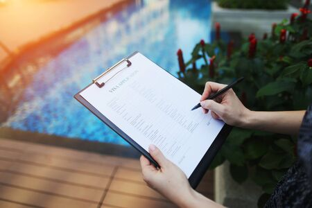 Foto de woman's hands sign or fill out visa application form for France against backdrop of new pool. concept of business trip, an appeal to travel agents for organization of tour. Front used with Open Font License - Imagen libre de derechos