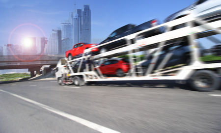 Foto de The trailer transports cars on highway with big city background - Imagen libre de derechos