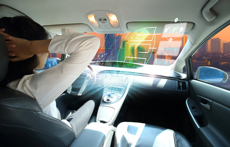 Foto per electric car or  intelligent car. connected car. Internet of Things. Heads up display(HUD).futuristic vehicle and graphical user interface(GUI).self-driving  mode , autonomous car, vehicle running self driving mode and a woman driver  - Immagine Royalty Free