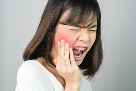 Photo pour Asian girl in white casual dress Show off the toothache, Maybe because of not maintaining good oral health. on a gray background gives a soft light. - image libre de droit