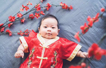 Photo pour Baby in red dress on blue cloth with flower and looking. Concept Chinese New Year. - image libre de droit