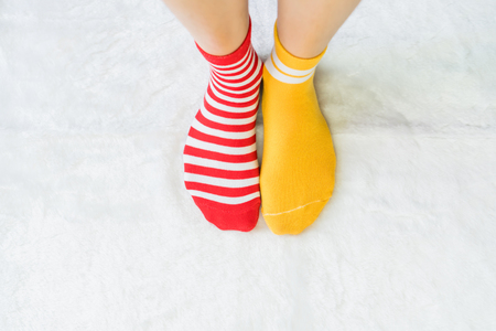 Photo pour Legs in socks two colors alternate, Red and yellow side stand on white fabric floor. - image libre de droit