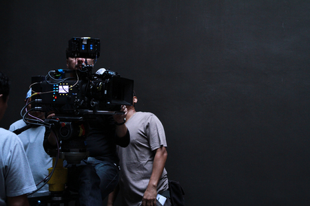 Photo pour A cameraman with his team working in studio for shooting a movie - image libre de droit