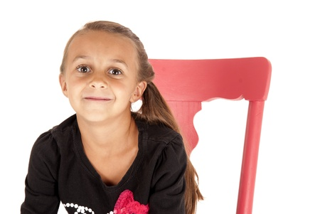 Girl in chair with a cheesy grin