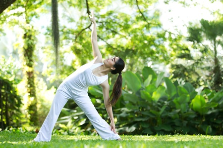 Foto de Woman in white Performing yoga in natural setting - Imagen libre de derechos