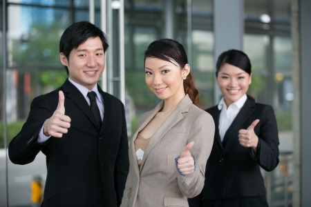 Cheerful Asian business men and women with thumbs up.