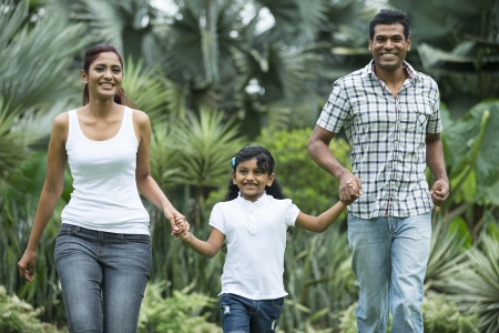 Happy indian family running together outdoors in the park