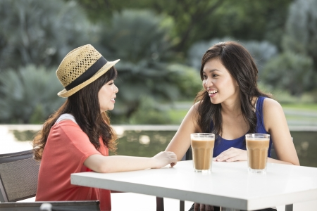 Photo for Two Chinese female friends Enjoying Cup Of Coffee - Royalty Free Image