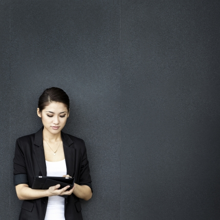 Asian business woman using digital tablet computer, leaning against a black wall.