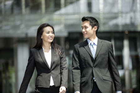 Happy Chinese Business colleagues walking outside office & talking to each other.