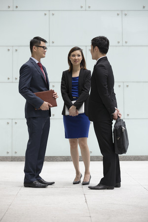 Happy Chinese Business colleagues outside the office talking to each other.