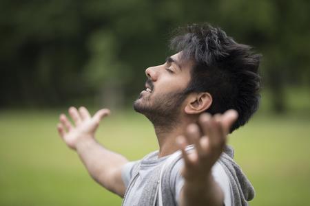 Foto de Asian man standing with arms raised outdoors. Concept about freedom, faith and celebration. - Imagen libre de derechos