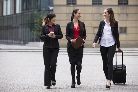 Three Happy Business women walking outside and talking to each other.