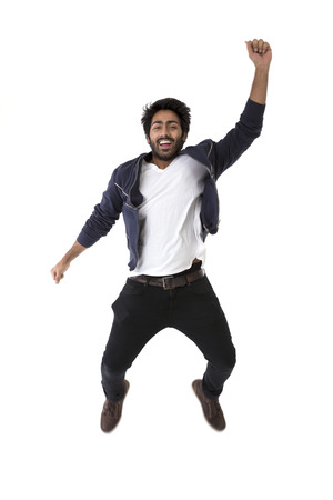 Foto de Excited Indian man jumping for joy. Isolated on white background. - Imagen libre de derechos