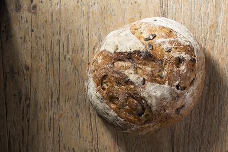 Foto de Above view of a rustic loaf of bread on an old wooden table. - Imagen libre de derechos