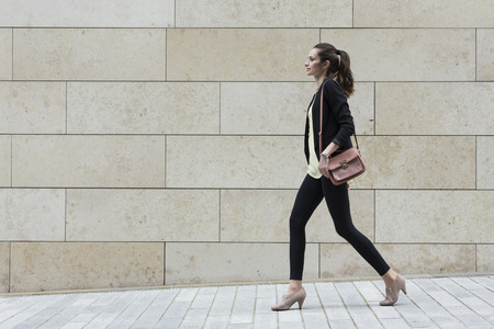 Photo pour Side view of a Caucasian Businesswoman walking on city street in front of modern marble wall. - image libre de droit