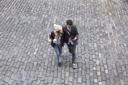 Photo for High angle view of a couple walking down the street using a Smart Phone. Young man and woman walking together. - Royalty Free Image