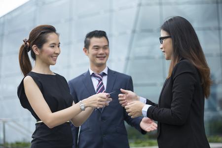 Foto de Asian Businesswoman presenting her business card to a female business collegue. - Imagen libre de derechos