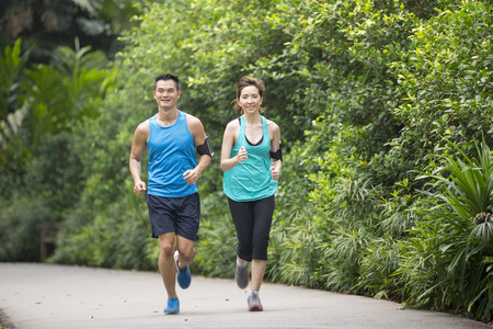 Photo pour Athletic Asian man and woman running outdoors. Action and healthy lifestyle concept. - image libre de droit