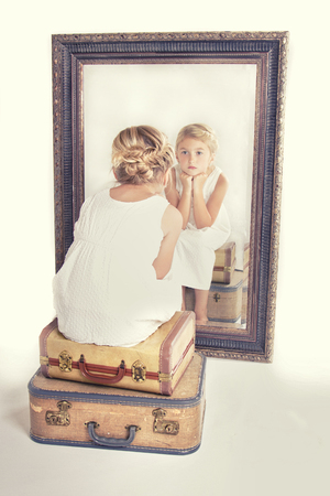 Photo pour Child or young girl staring at herself in a mirror, sitting on vintage luggage, with a fish tail braid in her hair. Vintage or retro filter applied. - image libre de droit