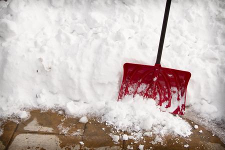 Foto de Red snow shovel in a snow bank on pavement - Imagen libre de derechos