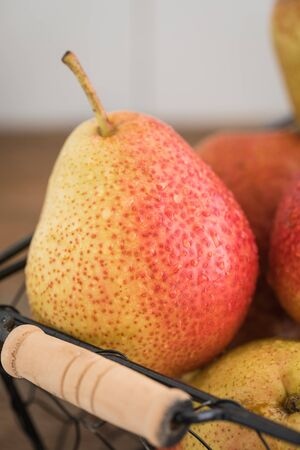 Fresh pears in the basket on the rustic wooden background