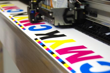 Photo pour Plotter head printing CMYK test on white paper. Large digital inkjet machine work. - image libre de droit