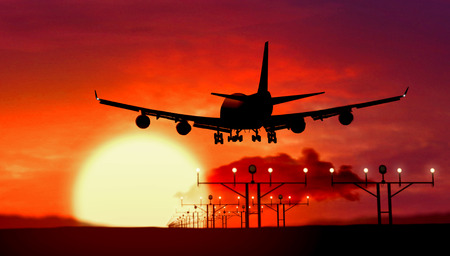 Foto de Airplane silhouette of Jumbo Jet lands at the airport during sunset. Shape of airplane and flashing runway lights. - Imagen libre de derechos