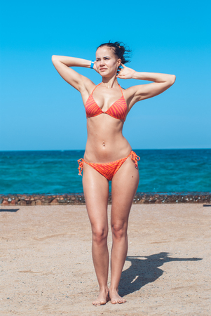 Foto de perfectly built Beautiful and young girl with wide hips in a striped orange swimsuit stands and Tans by placing her elbows in the sides against the backdrop of the blue sea. Vertical image - Imagen libre de derechos