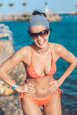 Foto de perfectly built Beautiful and young girl with wide hips in a striped orange swimsuit and sunglasses stands and Tans against the backdrop of the blue sea. she laughs showing her teeth. - Imagen libre de derechos