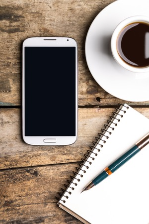 Foto de Smart phone with notebook and cup of strong coffee on wooden background. Cellphone with writing set with espresso - Imagen libre de derechos