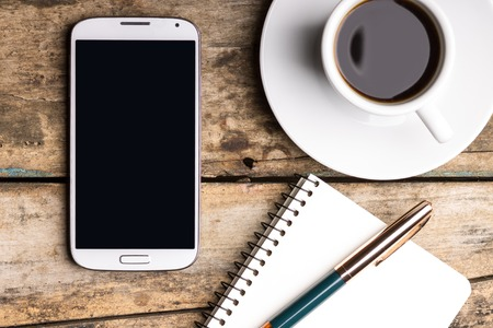 Foto de Smartphone with notebook and cup of strong coffee on wooden background. Cell phone with writing set with espresso - Imagen libre de derechos