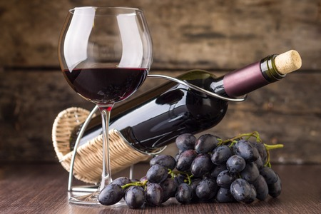 Photo pour Winery background. Elegant wineglass with bottle of red wine and cluster of grape. - image libre de droit