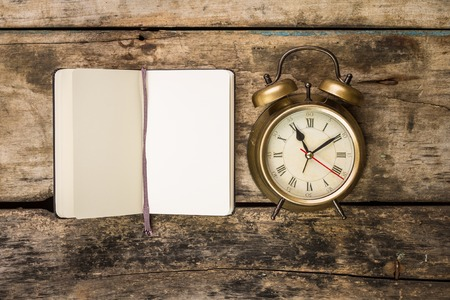 Photo for Open small notebook with retro-fashioned alarm clock . Top view writing vintage background - Royalty Free Image