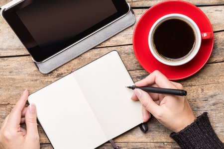 Foto de Young woman writing or drawing into notepad using tablet PC and enjoying cup of coffee. Top view freelancer workplace image - Imagen libre de derechos