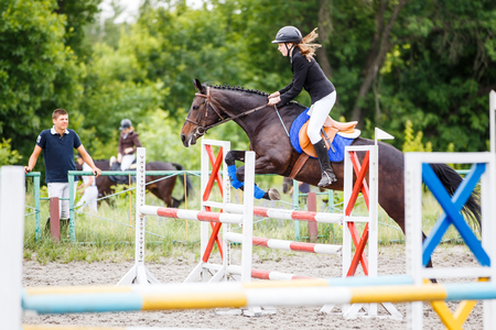 Photo pour Young rider girl training jumping with her trainer - image libre de droit