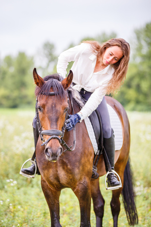 Photo for Young rider girl bent to horse for complimenting - Royalty Free Image