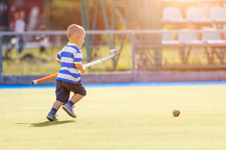 Photo for Small boy training playing field hockey with stick - Royalty Free Image