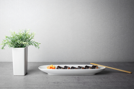 Photo pour Maki sushi served in long plate on grey table - image libre de droit