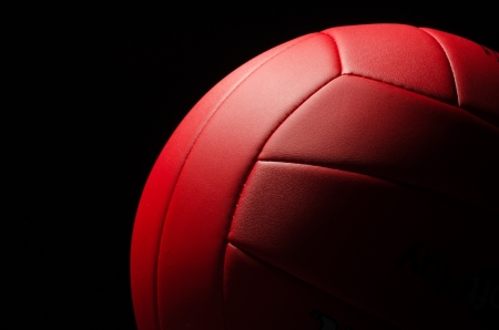 Red volley ball against a  black background