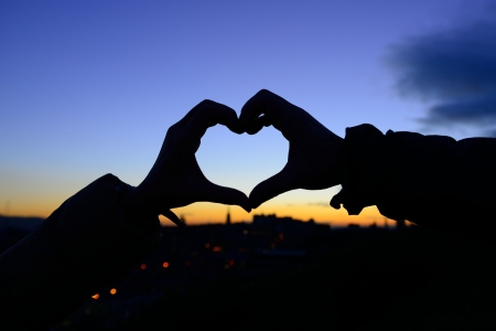Silhouette of hands in form of heart when sweethearts have touched in autumn with sunset at city background