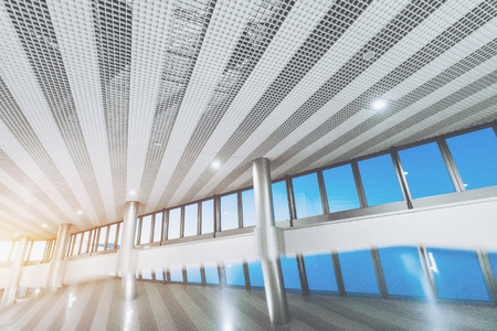 Photo pour Wide angel view of upper part of bright abstract interior: modern airport terminal or mall with checkered and striped ceiling, row of window, metal columns and strong reflections in the bottom - image libre de droit